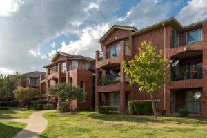 exterior brick building, stairways, balconies, patios, sidewalk, and trees