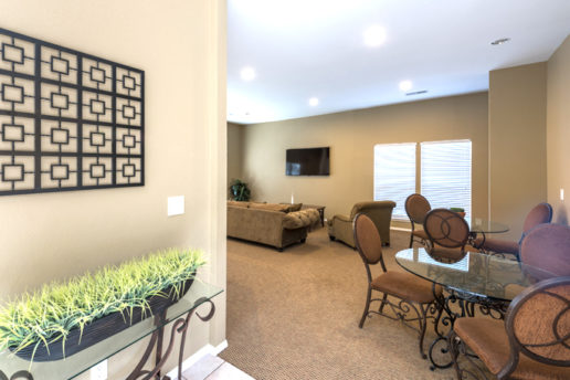 carpeted living room with tan walls, tan carpet, tables
