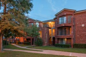 exterior brick building at night, stairways, balconies, sidewalks, and trees