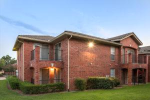 exterior brick building, balconies, patios, grass, and shrubs