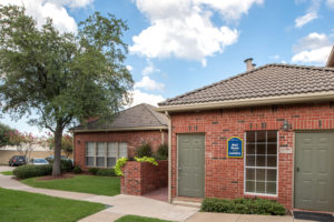 exterior of Mail Room, Laundry Room, red brick buildings with sidewalks and grass