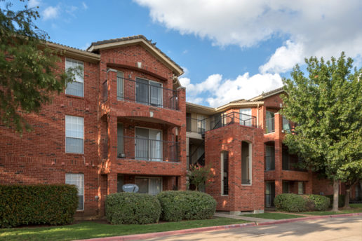 exterior brick building, stairways, balconies, patios, sidewalk, and trees