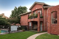 exterior brick building, stairways, balconies, patios, sidewalk, and trees overlooking pool