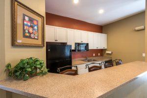 Kitchen with black refrigerator, burnt orange wall, tan wall, white cabinets, cream countertops, breakfast bar