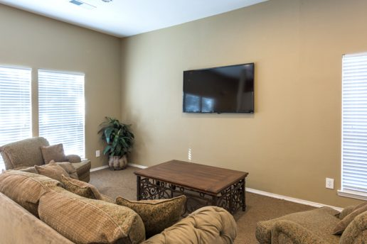 living room with tan walls, brown carpet, tan couch and chairs, plant, brown coffee table, and television