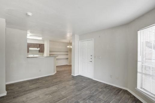 large wood floored room facing kitchen