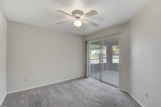 large carpeted room with ceiling fan and sliding glass door