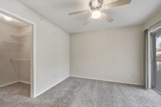 large carpeted room with ceiling fan