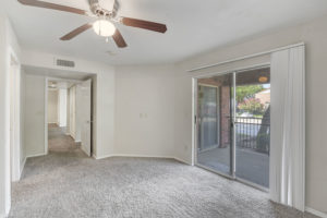 large room with ceiling fan and sliding glass door