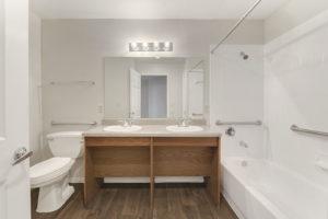 bathroom with large mirror and full bathtub